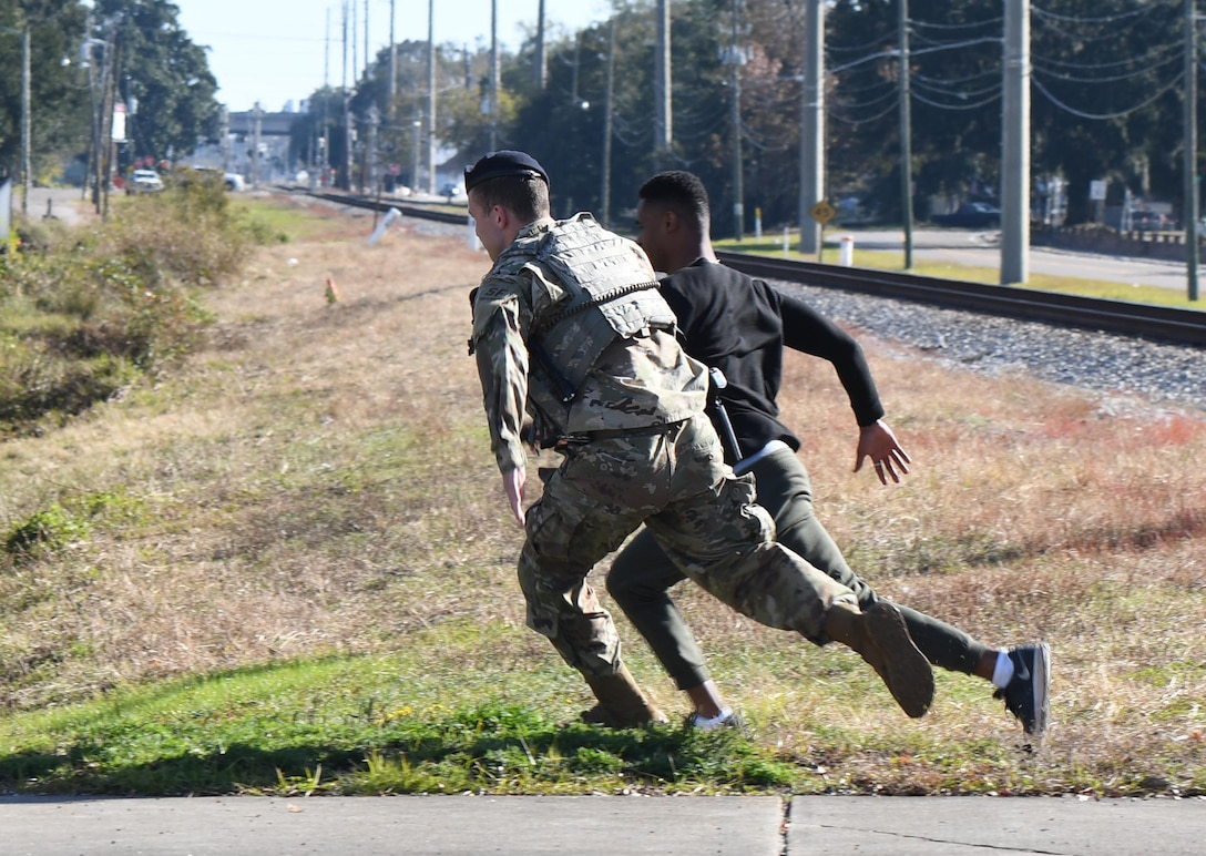 """U.S. Air Force Senior Airman Matthew Brooks, 81st Security Forces Squadron military working dog handler, pursues Airman Jair Semexant, 81st Medical Support Squadron logistics technician, who is portraying a """"protestor"""" attempting to breach the installation perimeter during the 81st SFS protest drill at Keesler Air Force Base, Mississippi, Dec. 12, 2018. The scenario included peaceful protestors expressing their first amendment right that further escalated to a riot when they felt they weren't being heard. The drill, which was a joint effort with the Biloxi Police Department, was conducted to control or prohibit demonstrations and protests. (U.S. Air Force photo by Kemberly Groue)"""