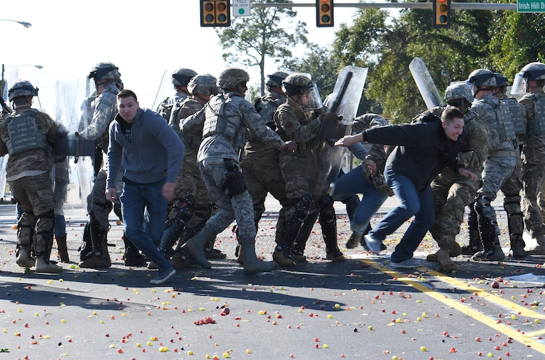 Members of the 81st Security Forces Squadron riot control team apprehend protestors during the 81st Security Forces Squadron protest drill at Keesler Air Force Base, Mississippi, Dec. 12, 2018. The scenario included peaceful protestors expressing their first amendment right that further escalated to a riot when they felt they weren't being heard. The drill, which was a joint effort with the Biloxi Police Department, was conducted to control or prohibit demonstrations and protests. (U.S. Air Force photo by Kemberly Groue)