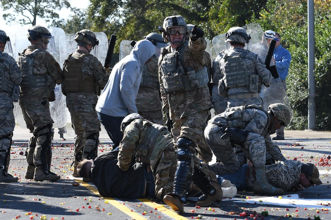 U.S. Air Force Master Sgt. Matthew Oleson, 81st Security Forces Squadron operations NCO in charge, yells out commands as members of the 81st SFS riot control team apprehend protestors during the 81st SFS protest drill at Keesler Air Force Base, Mississippi, Dec. 12, 2018. The scenario included peaceful protestors expressing their first amendment right that further escalated to a riot when they felt they weren't being heard. The drill, which was a joint effort with the Biloxi Police Department, was conducted to control or prohibit demonstrations and protests. (U.S. Air Force photo by Kemberly Groue)