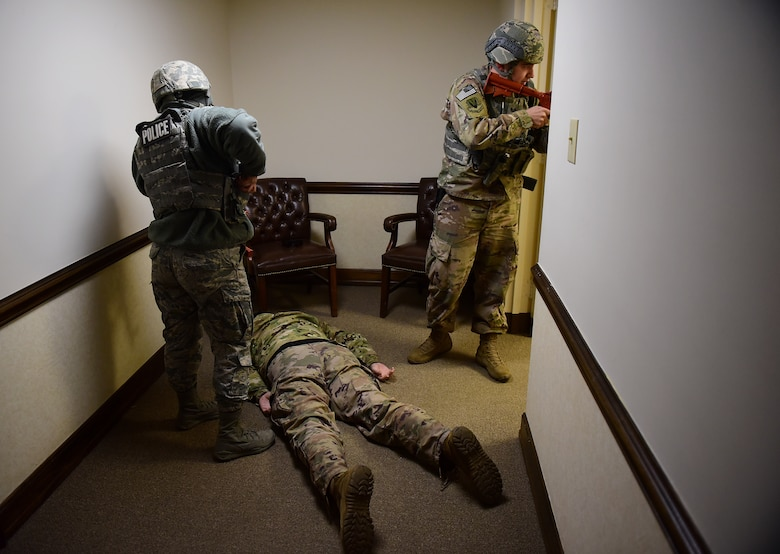 Airman 1st Class Nelly Lewis, 4th Security Forces Squadron patrolman (left), and Staff Sgt. Zackory Lollar, 4th SFS desk sergeant (right), prepare to arrest a simulated active shooter during a planned exercise Dec. 12, 2018, at Seymour Johnson Air Force Base, North Carolina. The 4th Fighter Wing utilizes realistic scenarios such as this one, to help keep Airmen and civilian government employees in a warrior mindset. (U.S. Air Force photo by Senior Airman Kenneth Boyton)