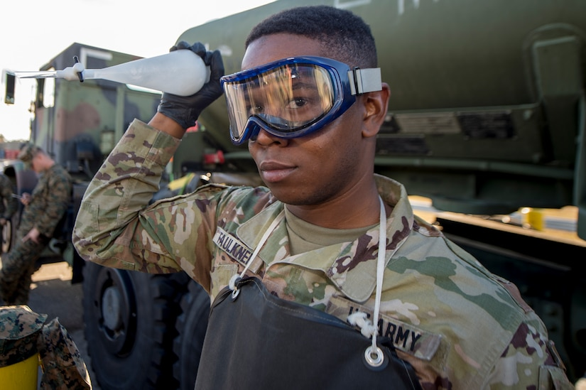 Army Sgt. Leroy Faulkner, a fuel supply specialist from Ft. Lee, Va., mixes fuel with water in order to test the fuel's content using a refractometer during a during a technical demonstration of the Expeditionary Mobile Fuel Additization Capability at the Charleston Defense Fuel Supply Point Dec. 6, 2018.