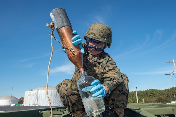 Marine Lance Cpl. Abril Garcia, a bulk fuel specialist from Marine Wing Support Squadron 172, Okinawa, Japan, retrieves a fuel sample during a technical demonstration of the Expeditionary Mobile Fuel Additization Capability at the Charleston Defense Fuel Supply Point Dec. 6, 2018.