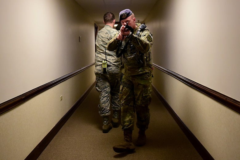 Senior Airman Daniel Johnson, 4th Security Forces Squadron military working dog handler, provides rear security for two responders from the 4th Civil Engineer Squadron during a planned active shooter exercise Dec. 12, 2018, at Seymour Johnson Air Force Base, North Carolina. The 4th Fighter Wing utilizes realistic scenarios such as this one, to help keep Airmen and civilian government employees in a warrior mindset. (U.S. Air Force photo by Senior Airman Kenneth Boyton)