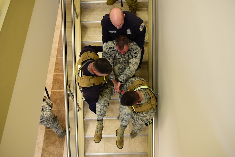 Chief Master Sgt. Stephen Cornelius, 4th Fighter Wing Command Chief, acts as a simulated victim and is carried down the stairs by three 4th Civil Engineer Squadron firefighters during a planned active shooter exercise Dec. 12, 2018, at Seymour Johnson Air Force Base, North Carolina. During the exercise, unsuspecting individuals are labeled injured or deceased to help create a more realistic exercise. (U.S. Air Force photo by Senior Airman Kenneth Boyton)
