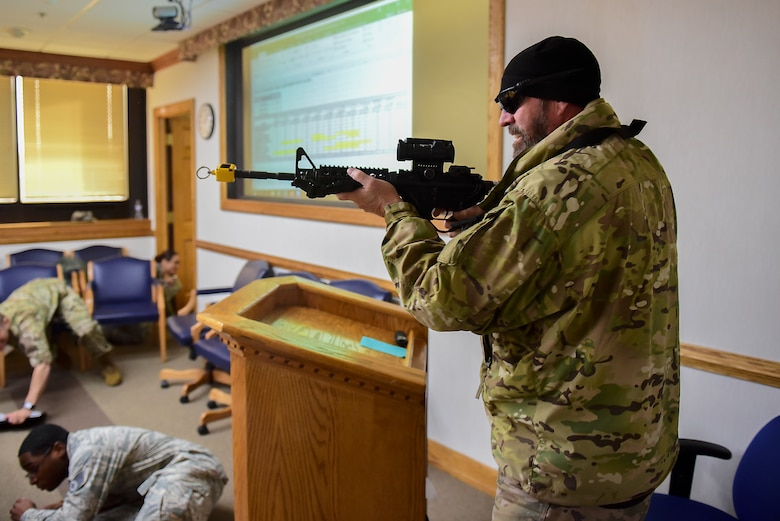 A simulated active shooter fires his weapon in a conference room during a planned exercise Dec. 12, 2018, at Seymour Johnson Air Force Base, North Carolina. During the exercise, the shooter's weapon used blank rounds which are designed to create a loud sound and flash without a projectile. (U.S. Air Force photo by Senior Airman Kenneth Boyton)