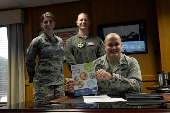 U.S. Air Force Col. Eric Carney, 97th Air Mobility Wing commander, holds the Combined Federal Campaign booklet while the Altus Air Force Base CFC team stands behind him, Dec. 13, 2018, at Altus AFB, Okla. The CFC is the largest and most successful annual workplace charity campaign, raising millions of dollars each year. (U.S. Air Force Photo by Senior Airman Jackson N. Haddon)