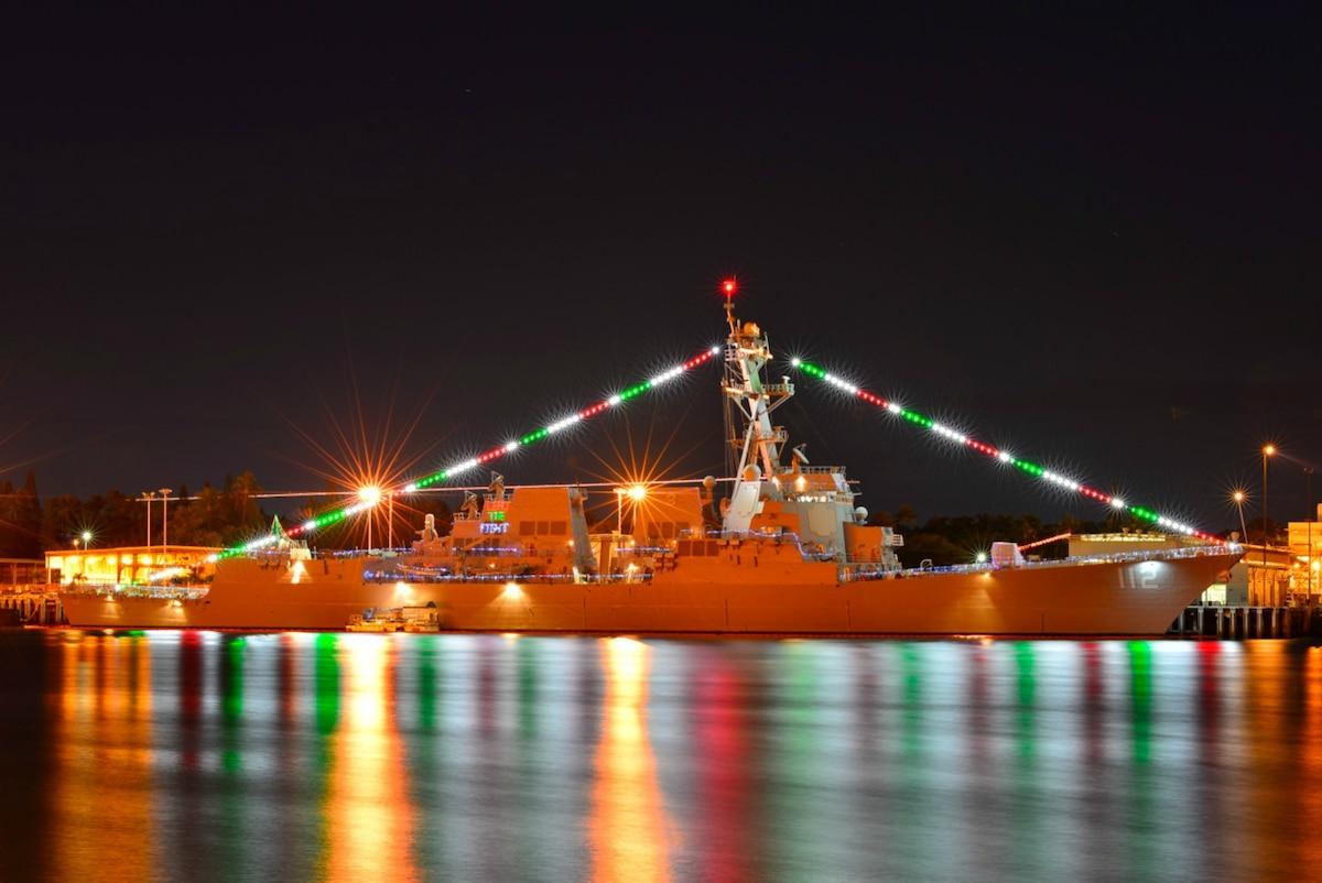 As ship lit up with lights is reflected in water.