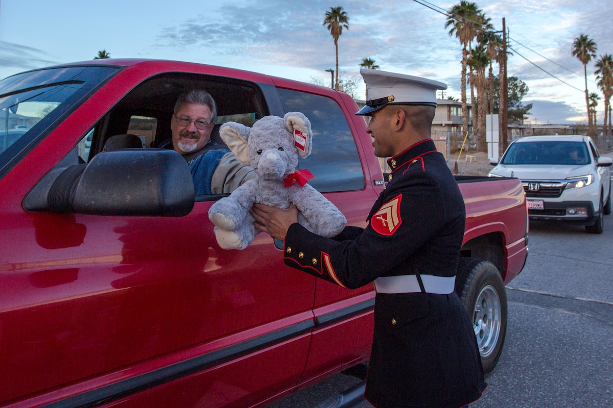 A Marine accepts a toy from a man in sitting inside a truck