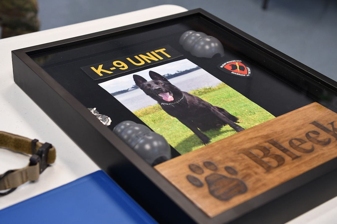 A shadow box is on display during a retirement ceremony for Bleck, 81st Security Forces Squadron military working dog, inside the Larcher Chapel at Keesler Air Force Base, Mississippi, Dec. 13, 2018. Bleck was accepted into military service August 2010, became fully certified as a patrol and drug detector dog in March 2011, and was assigned to Keesler shortly after. (U.S. Air Force photo by Airman 1st Class Suzie Plotnikov)