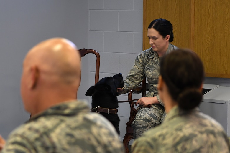 Bleck, 81st Security Forces Squadron military working dog, sits next to U.S. Air Force Capt. Samantha Giebel, 81st SFS operations officer, during his retirement ceremony inside the Larcher Chapel at Keesler Air Force Base, Mississippi, Dec. 13, 2018. After serving eight years and working alongside 11 handlers during his career, he was adopted by Giebel. (U.S. Air Force photo by Airman 1st Class Suzie Plotnikov)