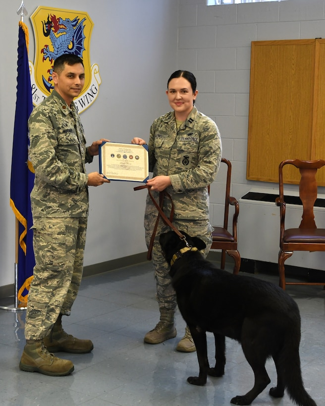 U.S. Air Force Maj. Jonathon Murray, left, 81st Security Forces Squadron commander, presents a certificate of appreciation to Bleck, 81st SFS military working dog, accepted by Capt. Samantha Giebel, right, 81st SFS operations officer, during a retirement ceremony at Keesler Air Force Base, Mississippi, Dec. 13, 2018. After serving eight years and working alongside 11 handlers during his career, he was adopted by Giebel. (U.S. Air Force photo by Airman 1st Class Suzie Plotnikov)