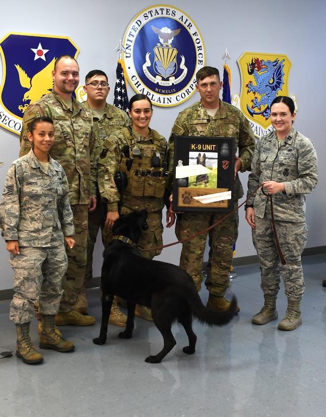 The 81st Security Forces Squadron military working dog section presents a shadow box to Bleck, 81st SFS MWD, during Bleck's retirement ceremony at Keesler Air Force Base, Mississippi, Dec. 13, 2018. After serving eight years and working alongside 11 handlers during his career, he was adopted by Giebel. (U.S. Air Force photo by Airman 1st Class Suzie Plotnikov)
