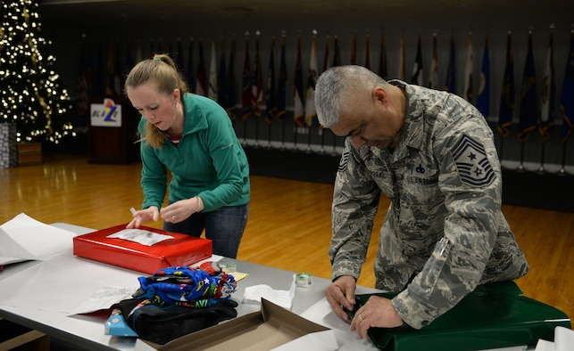Command Chief Master Sgt. Raul Villarreal Jr., 14th Flying Training Wing command chief, and Katie Steinback, spouse of Senior Master Sgt. Wade Steinback, 14th Flying Training Wing Staff Agency superintendent, wrap gifts during the Happy Irby Fund Shop and Wrap at the Club Dec. 12, 2018, on Columbus Air Force Base, Mississippi. (U.S. Air Force photo by Airman Hannah Bean)