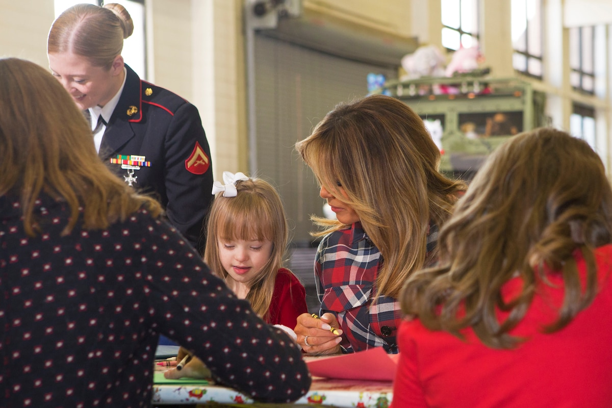 The first lady of the United States sits at a table next to a young girl