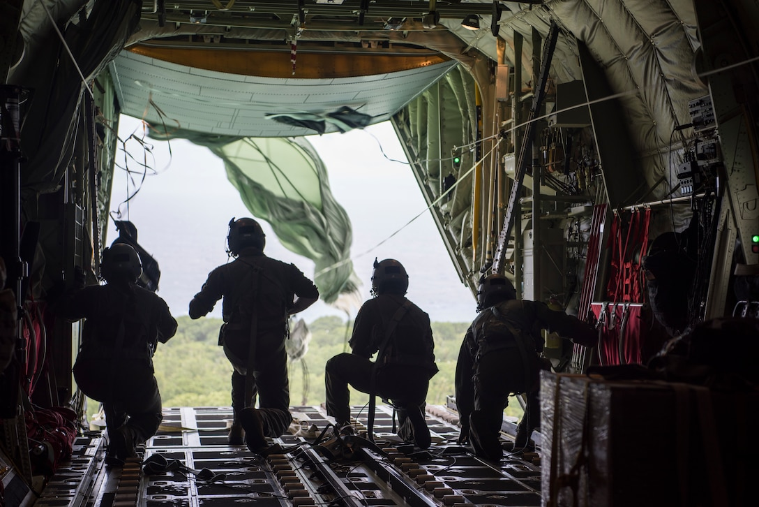 Gen. CQ Brown, Jr., Pacific Air Forces commander, assists a C-130J aircrew, from the 374th Airlift Wing, as they push airdrop bundles from the rear of the aircraft in support of Operation Christmas Drop 2018 Dec. 11, 2018. Brown's visit to Andersen Air Force Base, Guam, allowed him to familiarize himself with 36th Wing's mission and role in promoting peace and stability throughout the Indo-Pacific region.(U.S. Air Force photo by Senior Airman Zachary Bumpus)