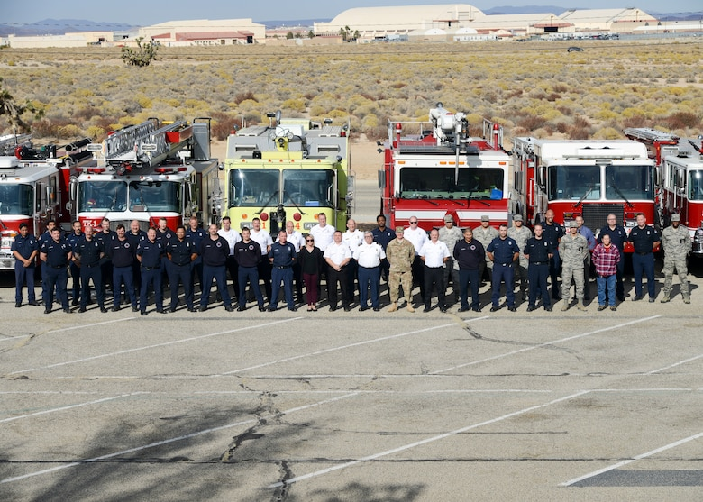 Members of the Edwards Air Force Base Fire and Emergency Services pose for a group photo with retiring Fire Chief, Michael Hurles, at Edwards Air Force Base, California, Nov. 16. (U.S. Air Force photo by Giancarlo Casem)