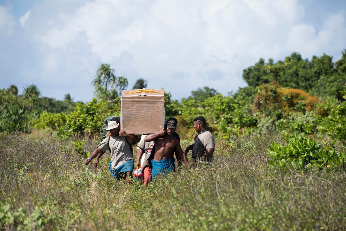 Residents carry a box of humanitarian supplies on their shoulders.