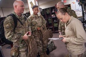 Tech. Sgt. Ashley Solum, right, 379th Expeditionary Operations Support Squadron aircrew flight equipment (AFE) technician, issues AFE gear to Chaplain (Maj.) Cody Hollist, left, and Staff Sgt. Daneasha Jenkins, center left, both assigned to the 379th Air Expeditionary Wing (AEW) chaplain office, Dec. 15, 2018, at Al Udeid Air Base, Qatar.