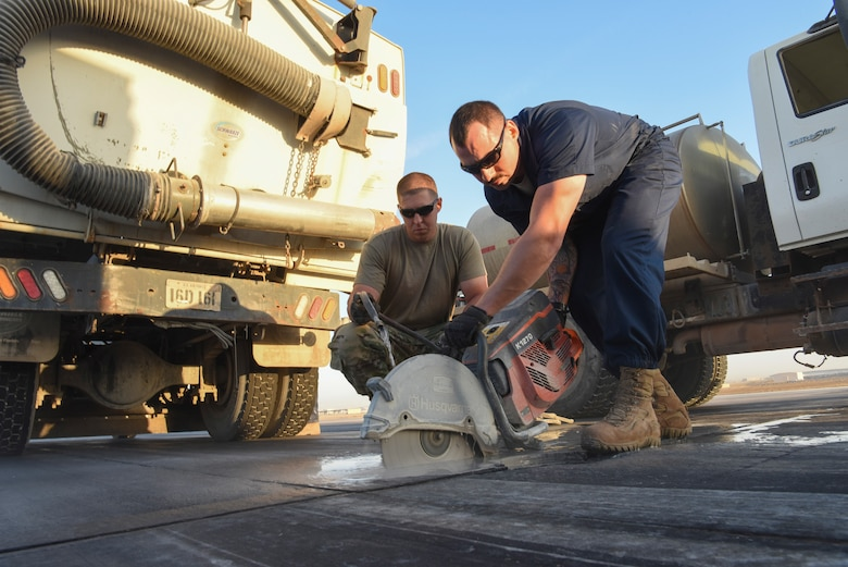 Senior Airman Charles Nelson, 380th Expeditionary Civil Engineering Squadron pavement and heavy equipment journeyman, uses water to enable Staff Sgt. Jesse Steinberg, 380th ECES pavement equipment journeyman, to cut a portion of the runway with a saw during runway repair at Al Dhafra Air Base, United Arab Emirates, Dec. 1, 2018.