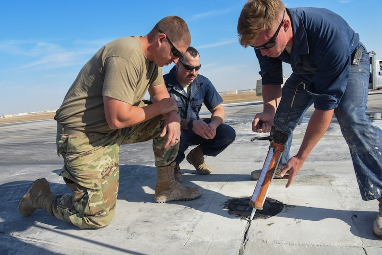 Senior Airman Charles Nelson (left) and Staff Sgt. Jesse Steinberg (middle) watches as Airman 1st Class Tyler Parker (right) seals the repaired runway area at Al Dhafra Air Base, United Arab Emirates, Dec. 1, 2018.