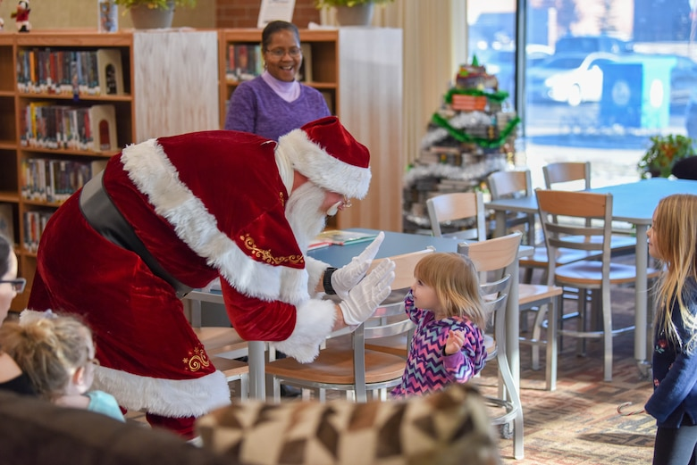 Santa Claus gives out high fives to kids at the Holbrook Library on Ellsworth Air Force Base, S.D., Dec. 13, 2018. Father Christmas visited the base to read a book with the good boys and girls of Ellsworth AFB. (U.S. Air Force photo by Tech. Sgt. Jette Carr)