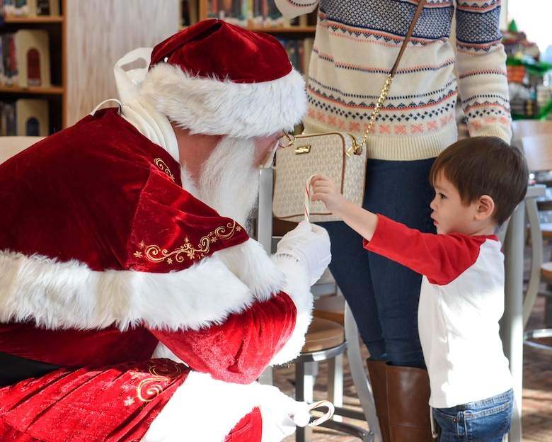 """Jolly old Saint Nicholas shares candy canes with children at Ellsworth Air Force Base, S.D., Dec. 13, 2018, during """"Santa and Me Story Time."""" Saint Nick was escorted by the Ellsworth AFB fire department to Holbrook Library, where he read a holiday book and visited with kids. (U.S. Air Force photo by Airman John Ennis)"""
