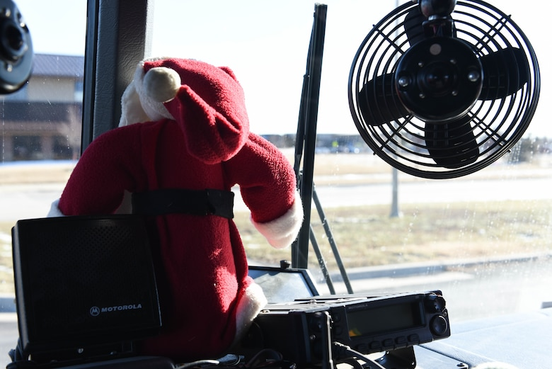 """A Santa Claus doll sits in the front window of a fire truck on Ellsworth Air Force Base, S.D., Dec. 13, 2018. Following a """"Santa and Me Story Time"""" event at the Holbrook Library, Airmen and their families were invited to the parking lot to tour a fire truck and visit with firefighters from the 28th Civil Engineer Squadron Fire Department. (U.S. Air Force photo by Airman John Ennis)"""