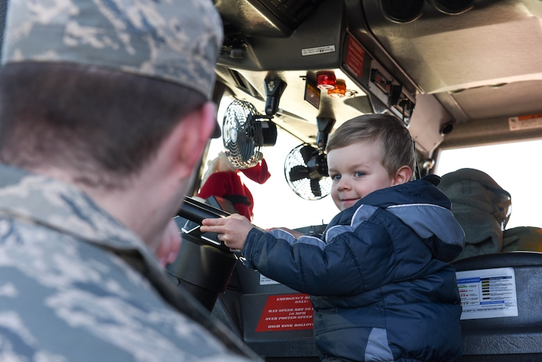 """A child at Ellsworth Air Force Base, S.D., is given the chance sit in the front seat of a fire truck on Dec. 13, 2018. Following a """"Santa and Me Story Time"""" event at the Holbrook Library, attendees were invited to the parking lot to tour a fire truck and visit with firefighters from the 28th Civil Engineer Squadron Fire Department. (U.S. Air Force photo by Airman John Ennis)"""