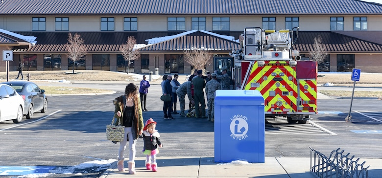 """Members of the 28th Civil Engineer Squadron Fire Department visit with families on Ellsworth Air Force Base, S.D., on Dec. 13, 2018, following the conclusion of """"Santa and Me Story Time"""" at the Holbrook Library. Firefighters escorted Santa Claus to the library earlier that day so he could read to the base's children. After Santa left, the firefighters invited the Airmen and their families to tour a fire truck. (U.S. Air Force photo by Airman John Ennis)"""