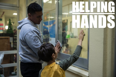 Lance Cpl. Derek S. Pulu helps a student clean a window Dec. 14, 2018 at Ginowan City, Okinawa, Japan. Marines and Sailors with Combat Logistics Battalion 4, Combat Logistics Regiment 3, 3rd Marine Logistics Group, volunteered at the AmerAsian School in Okinawa to help with various beautification projects around the school. The school conducts triannual clean-up projects before each semester. Pulu, a native of American Samoa, is a motor transportation operator with Transportation Service Company, CLB-4, CLR-3, 3rd MLG. (U.S. Marine Corps photo by Lance Cpl. Armando Elizalde)