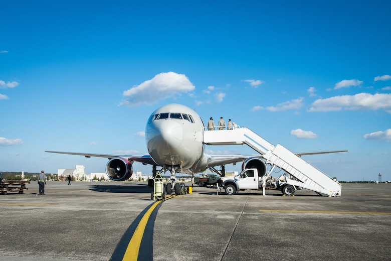 730th Air Mobility Squadron Airmen prepare for passengers to exit a Boeing 767-800ER aircraft