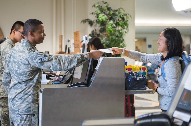 U.S. Air Force Senior Airman Anthony Johnson, 730th Air Mobility Squadron passenger service agent, hands a pamphlet to a passenger during check-in
