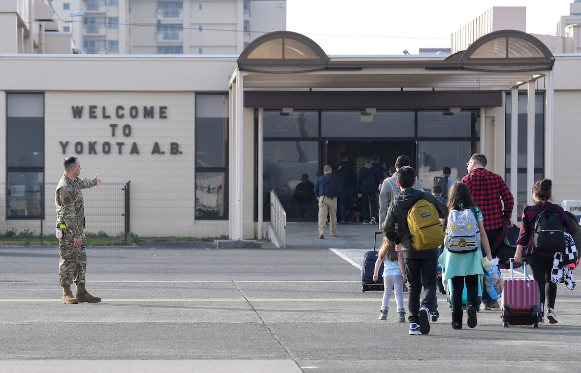 Airman 1st Class Alexander Blankenship, 730th Air Mobility Squadron passenger service agent, guides passengers to the entrance of the Yokota Air Base, Japan, Passenger Terminal