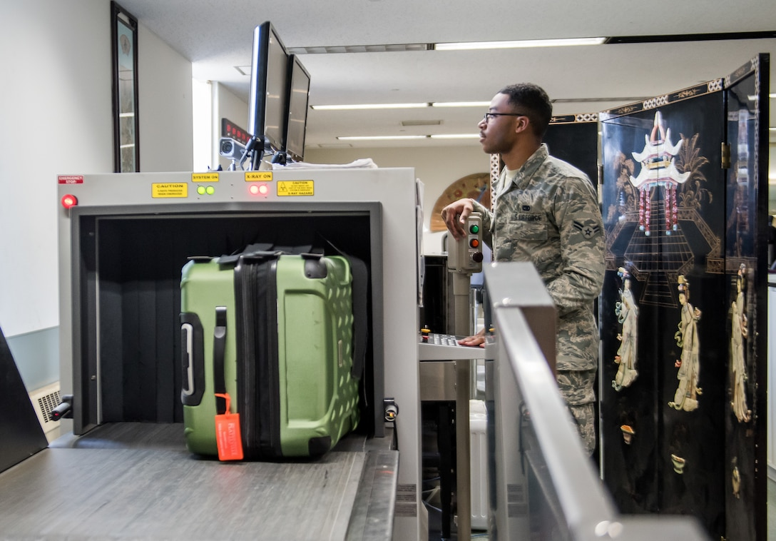 Airman 1st Class Malic Folwer, 730th Air Mobility Squadron passenger service agent, processes baggage through an x-ray machine