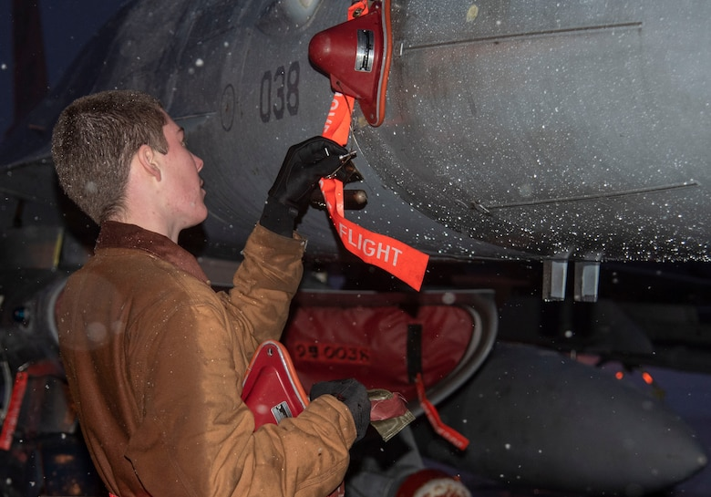 U.S. Air Force Airman 1st Class Avery Fortenbery, a 13th Aircraft Maintenance Unit crew chief, installs the lower pin on an F-16 Fighting Falcon at Misawa Air Base, Japan, Dec. 11, 2018. The aircraft-safe maintenance procedures communicate to the rest of the crew the aircraft is cleared to have post-flight maintenance work performed on it. (U.S. Air Force photo by Airman 1st Class Genesis Tejada)