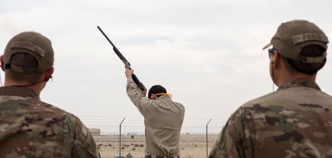 Tyler Adams, United States Department of Agriculture wildlife biologist, watches as Senior Master Sgt. Kenneth Riff, 443rd Air Expeditionary Squadron safety representative, fires off one of the pyrotecnics used to deter birds Dec. 3, 2018, at an undisclosed location in Southwest Asia. Although the main focus of this training was to deter animals, Airmen were also trained to maintain a list of all animals in their respected area, including endangered species.