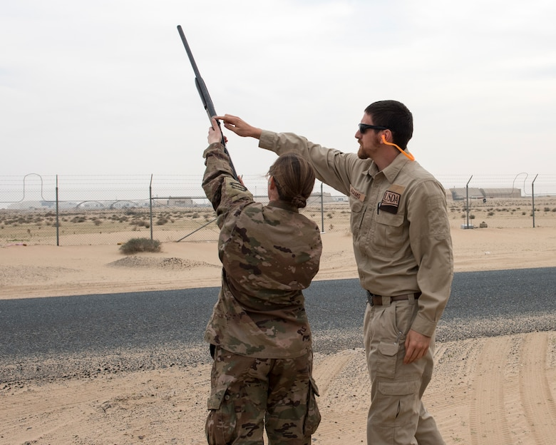 Tyler Adams, United States Department of Agriculture wildlife biologist, shows an Airman where to place her hands while firing a rifle used to shoot pyrtecnics, during the first ever Bird/wildlife Aircraft Strike Hazard program training at an undisclosed location in Southwest Asia, Dec. 3, 2018. Since 2016 nearly three million dollars have been spent on wildlife related damages in the area of responsibility.