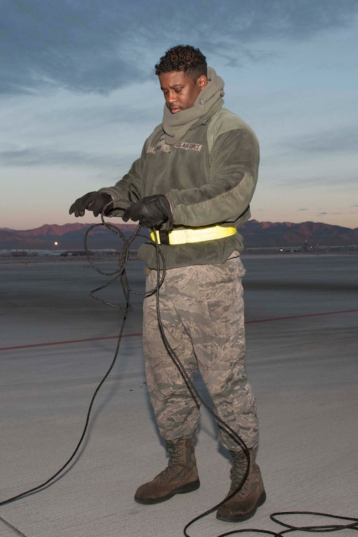 U.S. Air Force Staff Sgt. Jamall Fryer, 11th Aircraft Maintenance Unit crew chief, prepares for an early morning sortie at Nellis Air Force Base, Nevada, Dec. 11, 2018.  Fryer, an active-duty Airman, served alongside Reserve Citizen Airman during the biannual Weapons School Integration exercise.  The two components regularly work together as part of the total force integration model. (U.S. Air Force photo by Master Sgt. Ted Daigle)