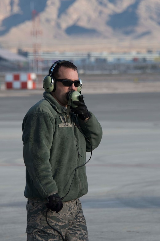 U.S. Air Force Tech. Sgt. Rick Poff, 307th Aircraft Maintenance Squadron crew chief, communicates with B-52 Stratofortress air crew prior to a sortie, Dec. 11, 2018 at Nellis Air Force Base, Nevada.  He was on hand, along with other active-duty and Reserve Citizen Airmen maintainers, to support the the biannual Weapons School Integration exercise. (U.S. Air Force photo by Master Sgt. Ted Daigle)
