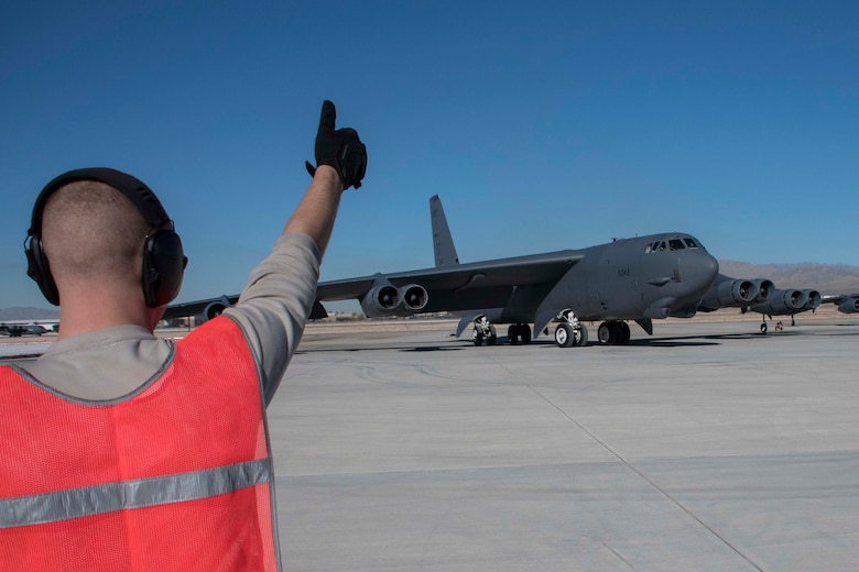 U.S. Air Force Senior Airman Alexander Horrocks, 11th Aircraft Maintenance Unit crew chief, gives a thumbs up to a departing B-52 Stratofortress at Nellis Air Force Base, Nevada, Dec. 11, 2018.  As part of the total force integration model, Horrocks, an active-duty Airman, served alongside Reserve Citizen Airmen maintainers from Barksdale Air Force Base, Louisiana to support the biannual Weapons School Integration exercise.  The Airmen work alongside one another both at Barksdale AFB and in forward locations.  The TFI leverages the continuity and knowledge base of the Air Force Reserve to serve as a force multiplier. (U.S. Air Force photo by Master Sgt. Ted Daigle)