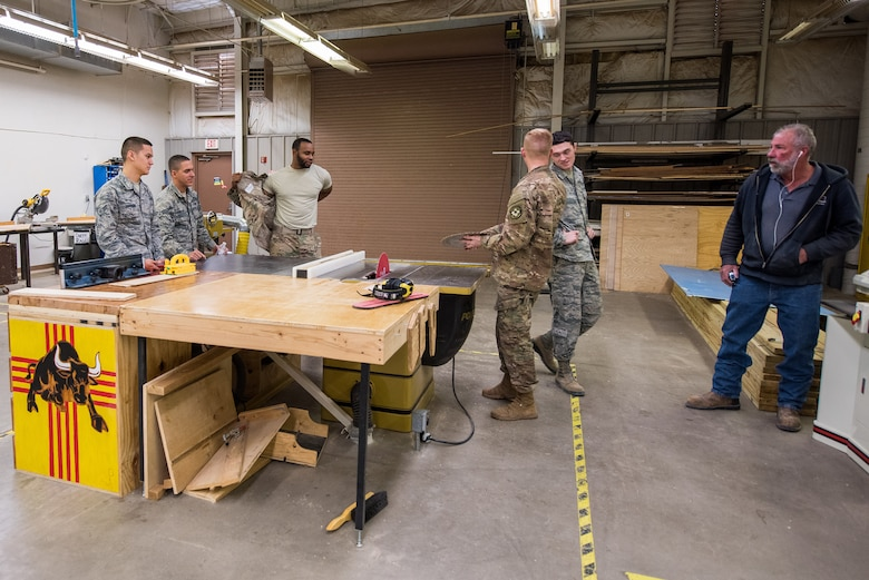 Members of the 27th Special Operations Civil Engineer Squadron structures shop have a briefing on how to properly replace a table saw blade at Cannon Air Force Base, New Mexico, Dec. 12, 2018. When a table saw is not powered on, Airmen still practice proper safety techniques as if it was. (U.S. Air Force photo by Airman 1st Class Vernon R. Walter III)