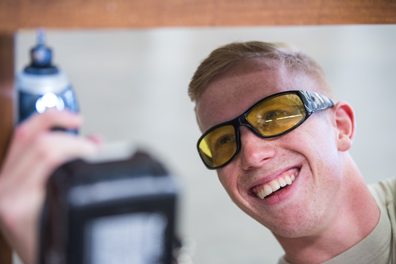 Senior Airman Dawson White, 27th Special Operations Civil Engineer Squadron structural journeyman, laughs while drilling in a replacement screw at Cannon Air Force Base, New Mexico, Dec. 12, 2018. When working, proper eye protection must be worn to prevent injury. (U.S. Air Force photo by Airman 1st Class Vernon R. Walter III)