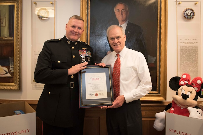 SECNAV Richard Spencer receiving Toys for Tots Commanders Award from CMFR at the annual SECNAV Holiday Party.