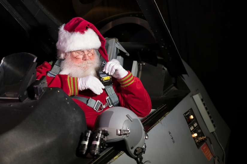 Santa buckles up in the cockpit of a fighter jet.