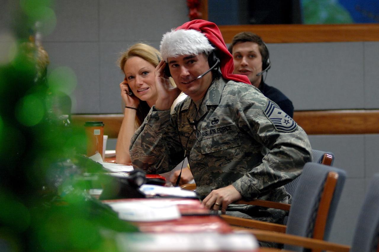 An airman wearing a Santa hat answers phone calls.