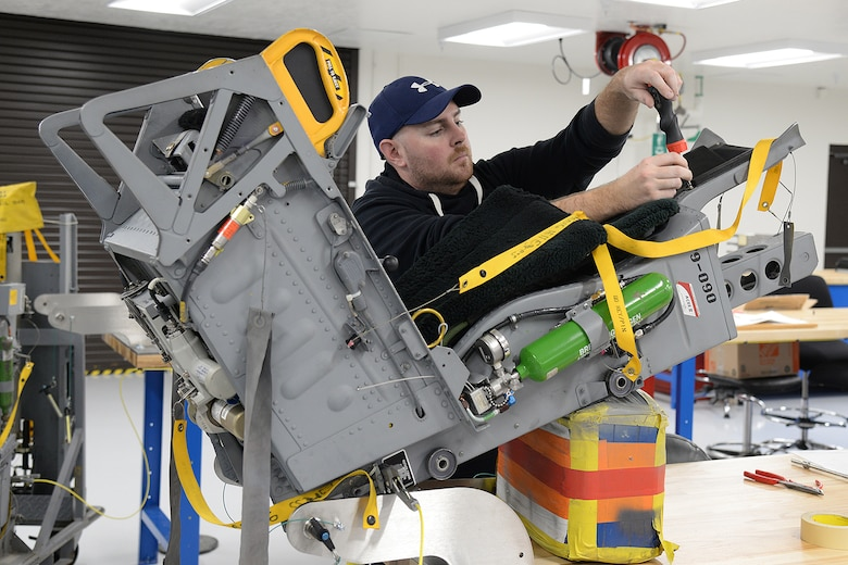 Sean Donnelly, 576th Aircraft Maintenance Squadron technician, installs a head rest assembly on an ACES II ejection seat Dec. 12, 2018, at Hill Air Force Base, Utah. The 576th AMXS opened the doors of its new egress repair facility that includes an expanded working area with an administration section, training section, tool room, explosive storage, and three separate work areas to separate the ACES II seat repairs from the F-35 Martin-Baker seat repairs. (U.S. Air Force photo by Alex R. Lloyd)