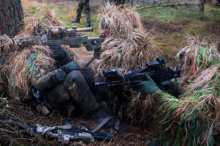 Marines and soldiers sit on the ground wearing grassy camouflage.