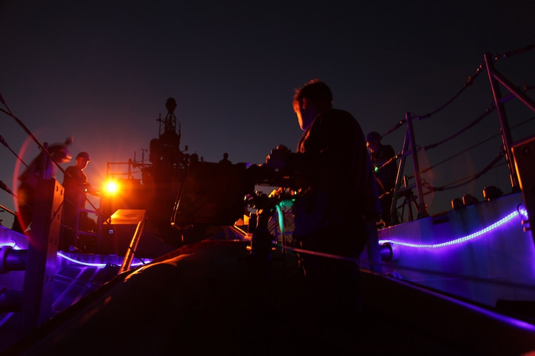 Service members work on board a military ship at night.