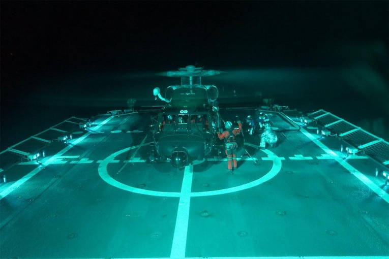 Coast Guard crewmembers refuel a helicopter.