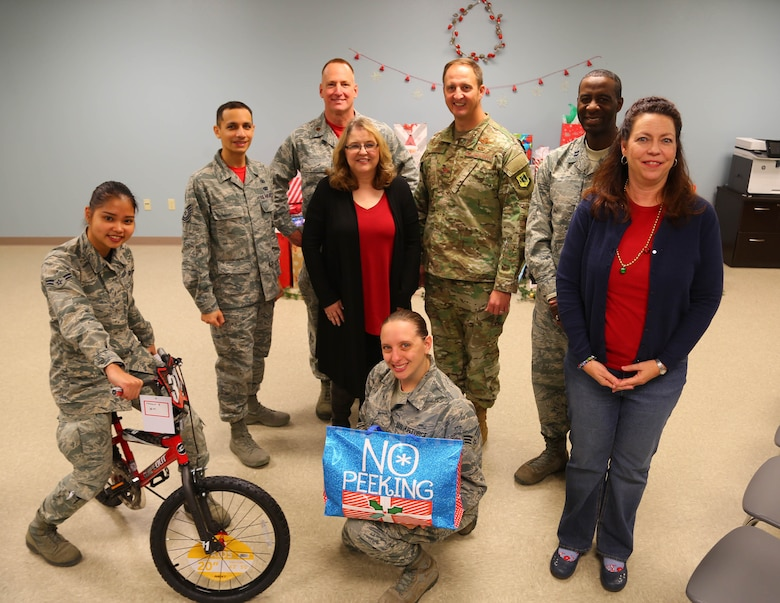 Col. Julian Cheater, 432nd Wing/432nd Air Expeditionary Wing  commander, Kimberly Guerino, Indian Springs School registrar, and Kelly Miles, Indian Springs School counselor, gather for a photo with members of the Human Performance Team and Airmen volunteers who collected, wrapped and coordinated delivery of gifts for Indian Springs Schools students at Creech Air Force Base, Nevada, Dec. 14, 2018. During the past seven years, Creech Airmen have donated roughly 800 presents to children in the local area during the Holidays. (U.S. Air Force photo by Tech. Sgt. Dillon White)